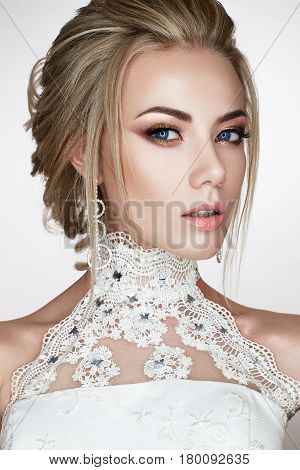A young girl in the image of a bride in a wedding dress and beautiful shiny earrings. A beautiful model with a bright makeup and perfect skin. Beauty of the face. Photo taken in the studio.