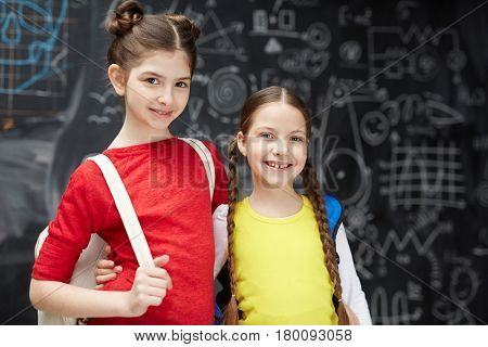 Pretty youngsters with backpacks looking at camera