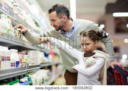 Capricious daughter asking her father to buy her tasty yoghurt in supermarket