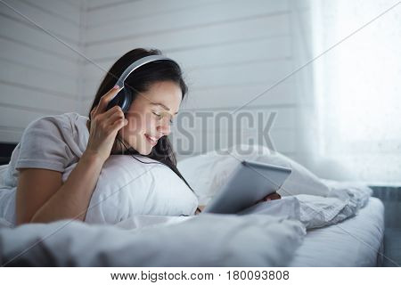 Girl with headphones and touchpad listening to music in bed