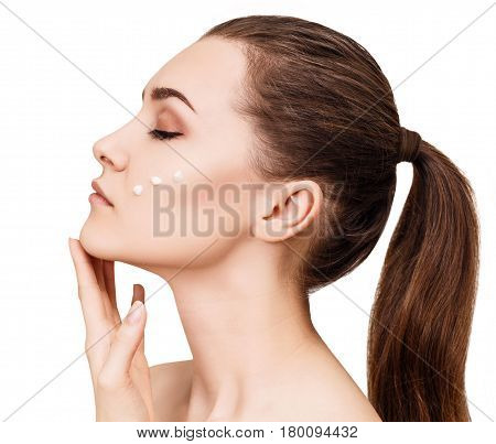Beautiful sensual woman with cream drops on cheek. Isolated on white.