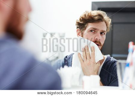 Young man blotting his irritated skin by towel