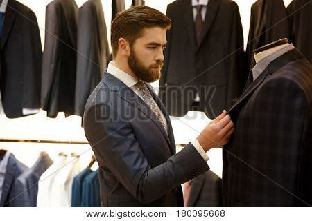 Side view of bearded man in suit choosing a jacket in shop