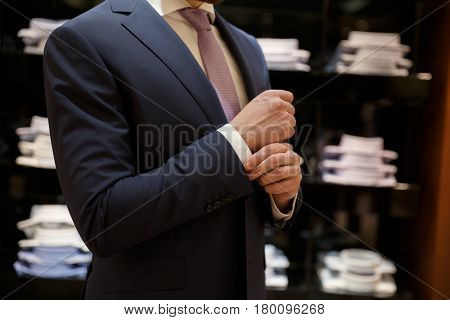 Cropped image of Man buttons up his shirt in a shop