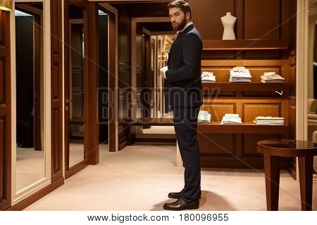Side view of serious man which tries on a suit and looking at camera being in a shop. Full length portrait