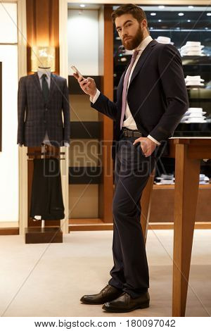 Vertical image of bearded man in suit  holding smartphone in his hand and holding one arm in pocket while looking at camera. Full length portrait
