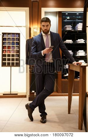 Full length portrait of serious bearded man in suit holding smartphone and looking at camera while being in a shop. Vertical image