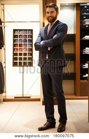 Full length portrait of a smiling bearded man in suit standing with crossed arms in a shop and looking at camera. Vertical image