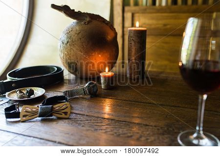 Men's rings in bronze plate, watch and a glass of wine on a wooden table with burning candles. Men's accessorizes, necktie, belt, watch
