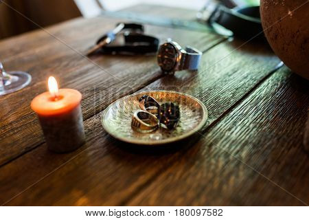 Bronze plate with men's rings on a wooden table with burning candles. Men's accessorizes, necktie, watch