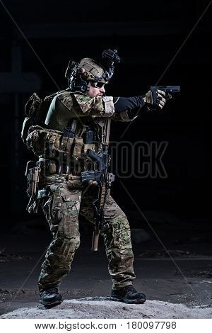 Special forces soldier with night vision device and gun on dark background