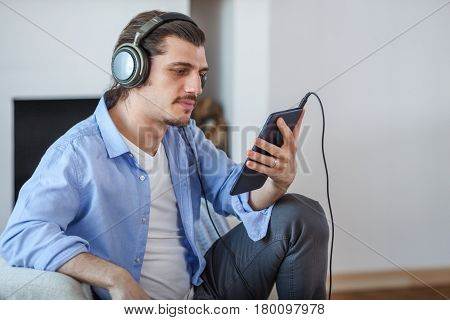 Handsome guy listening to music on internet with dark blue tablet on sofa