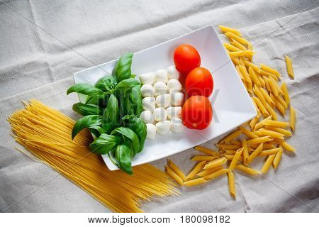 Tomatoes mozzarella raw pasta and green basil leaves on gray tablecloth