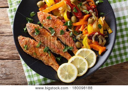 Roasted Red Mullet With Garnish Of Stewed Vegetables Close-up On A Plate. Horizontal Top View