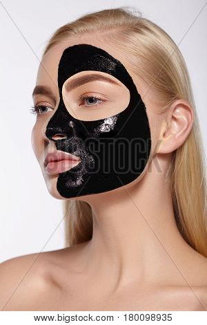 The face of the girl with a black mask on her face. Face care, cosmetics, spa.