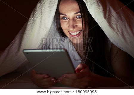 Close-up shot of a female using a phone under the blanket. Surprised female with a tablet at night. Lying in the bed at night