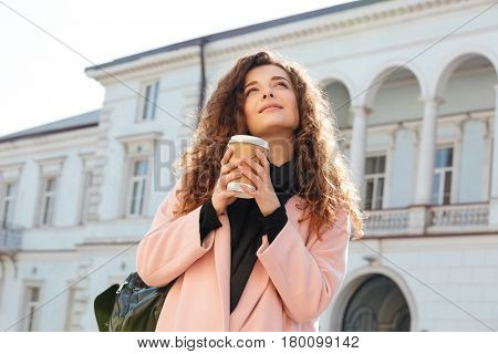 View from below of woman in coat holding cup of coffee and looking away