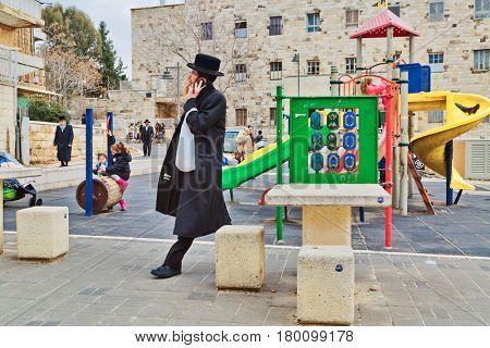 JERUSALEM, ISRAEL - DECEMBER 29, 2016: Orthodox Jewish man with mobile phone walk at street at the playground in jewish quarter.