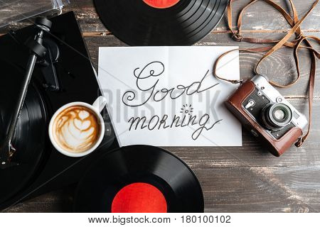 Photo of table with record-player, retro camera, sheet of paper and records. Good morning