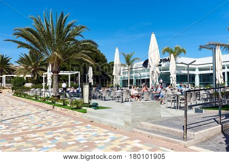 Punta Prima Spain - March 28 2017: Tourists sitting in a seafront cafe. Punta Prima is a popular tourist place. Province of Alicante. Southern Spain