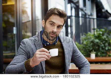 man holding coffee cup and thinking city life