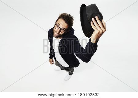 Gap tooth guy lifting hat to camera