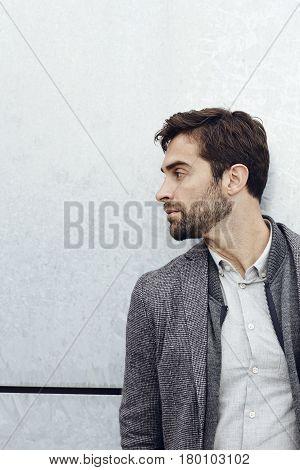Stubble guy in grey jacket looking away