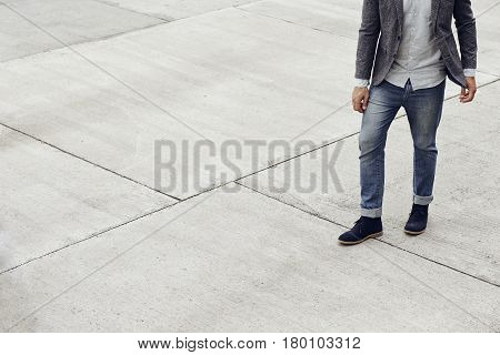 Dude in jeans walking on pavement low section