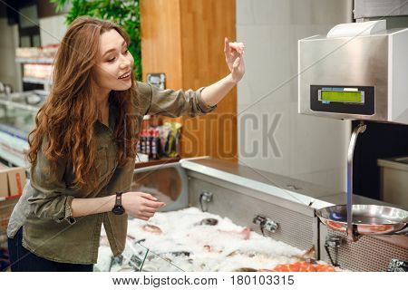 Side view of a happy woman choosing fish in supermarket