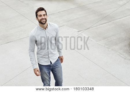 Smiling guy in grey shirt and jeans