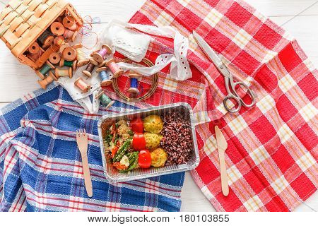 Desktop with lunch box healthy food delivery for dressmaker. Flat lay shot of foil container with diet meal for fashion designer at workplace. Healthy nutrition
