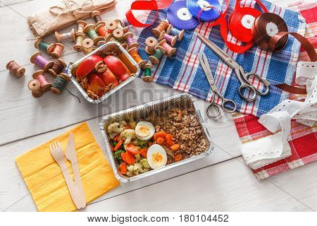 lunch box healthy food delivery for dressmaker. Closeup shot of foil container with diet meal for fashion designer at workplace. Healthy nutrition with eggs, vegetables and proteins