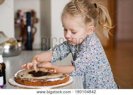 Cute little girl enjoying a homemade pizza holding a slice in her hand as she sits at the table looking at the camera with a smile.