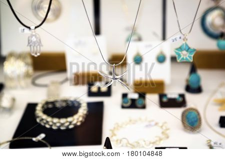 Silver star and other jewelry in a shop window closeup.Jewelry in shop blur background
