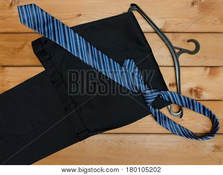 Pants tie and hanger on wooden table background