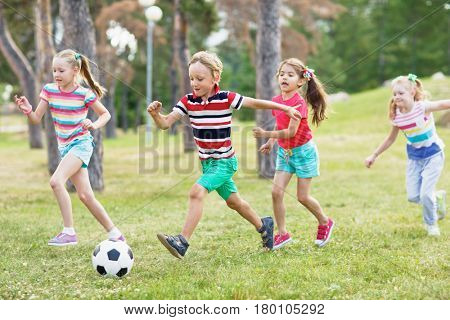 Elementary school kids in summer wear playing soccer on green lawn in park