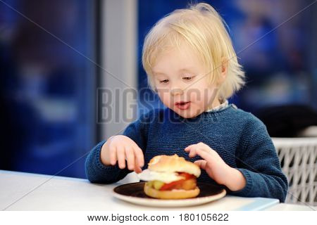 Cute Blonde Boy Eat Hamburger At Fast Food Restaurant