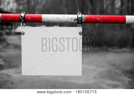 Barrier with a blank white signboard on a Road