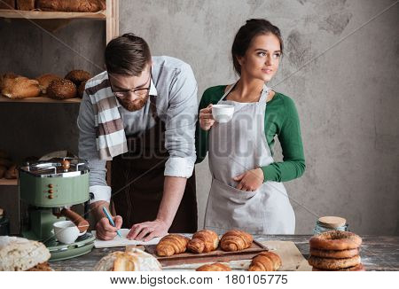 Handsome man writing recipe while his beautiful woman drinking cofee in kitchen