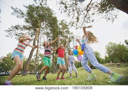Low angle view of excited children playing games with beach ball in city park on a summer day