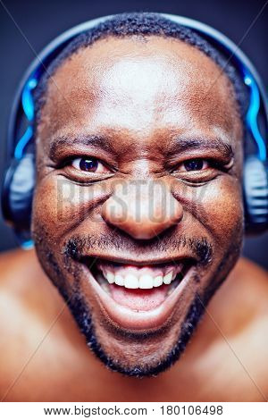 Close-up shot of funny African American music lover looking at camera and making faces against black background