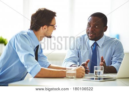 Waist-up portrait of Afro-American businessman in formalwear discussing promising project with his male colleague while sitting in meeting room
