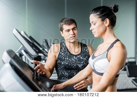 Portrait of muscular personal instructor explaining to fit woman how to set up elliptical machine for exercise in modern gym
