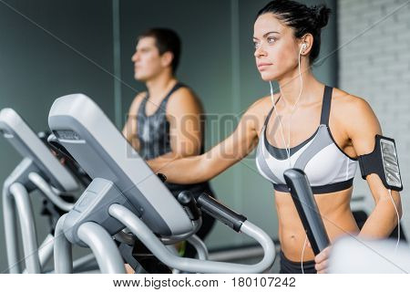 Portrait of beautiful  sportive brunette woman exercising using elliptical machine and listening to music next to fit man during workout in modern gym