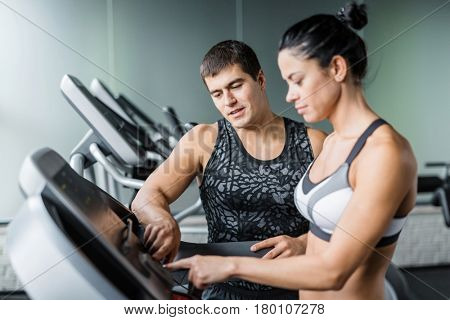 Portrait of muscular personal instructor explaining to fit woman how to use elliptical machine for exercise in modern gym