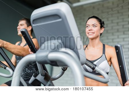 Low angle portrait of beautiful  sportive brunette woman  exercising using elliptical machine  next to fit man, both smiling during workout in modern gym