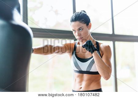 Portrait of strong muscular brunette woman training boxing with punching bag against window of sports center, looking intimidating and powerful