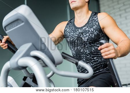 Closeup portrait of muscular sportive man  running using elliptical trainer during workout in modern gym