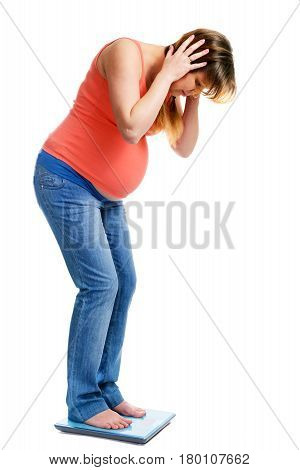 A cute pregnant woman shocked on scale isolated on white