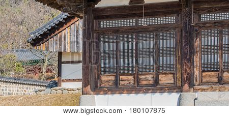 Oriental lattice work on doors of wooden building in a local woodland park in South Korea